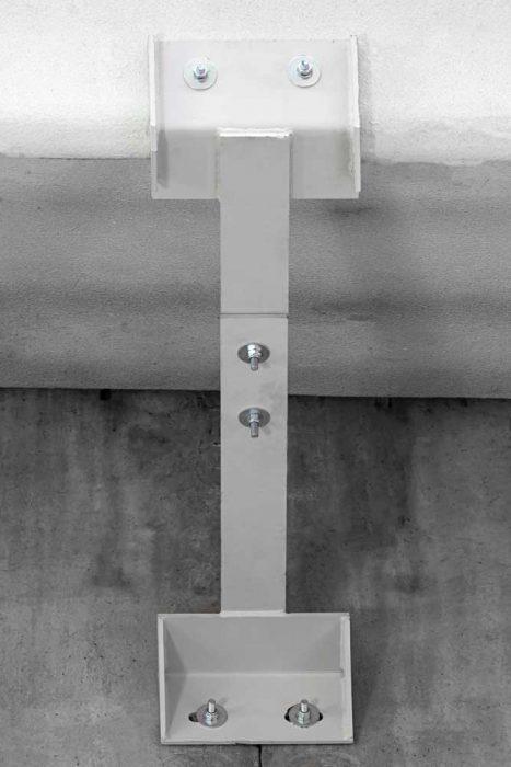 Sistema di ritenuta del pannello tramite profili metallici connessi al tegolo di copertura, finalizzato a prevenirne il ribaltamento fuori piano.