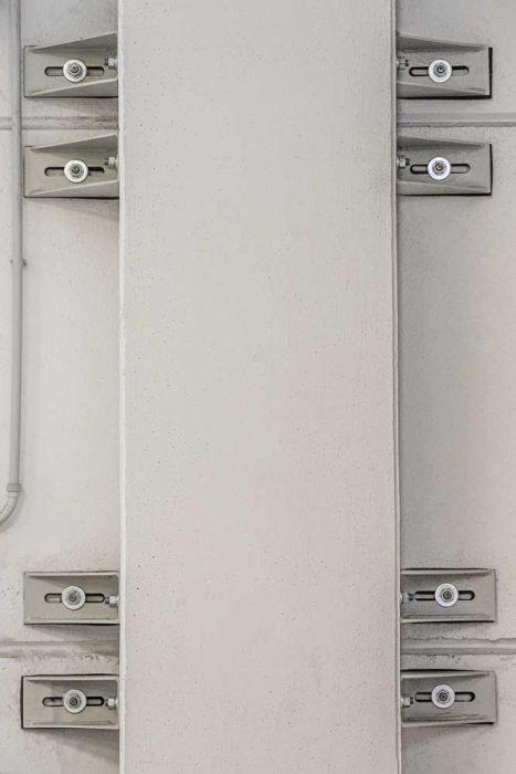 pilastro tramite profilo angolare con asola orizzontale per consentirne lo scorrimento.